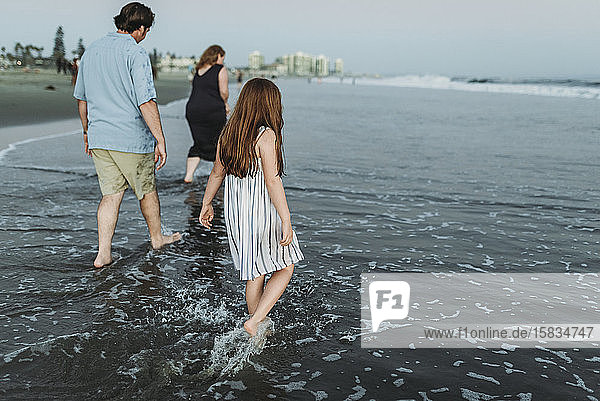 Rückansicht einer Familie  die in der Abenddämmerung ins Meer geht