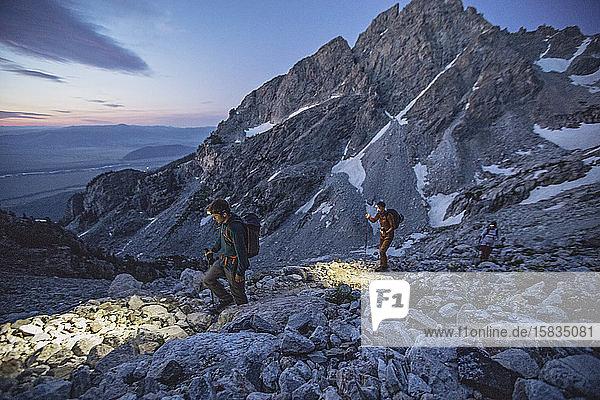 drei Wanderer mit Lichtern gehen einen Pfad in den Tetons entlang  Sonnenaufgang