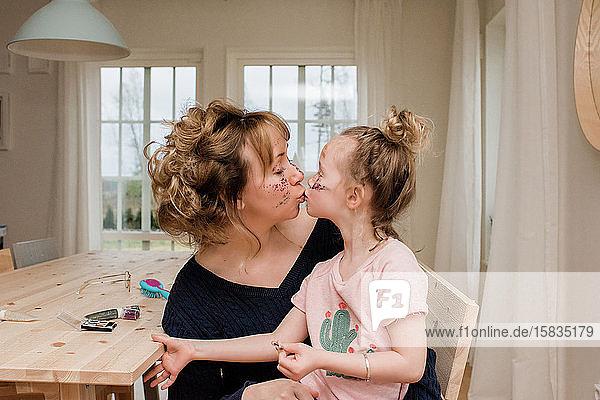 Mutter küsst Tochter  während sie zu Hause mit Make-up spielen