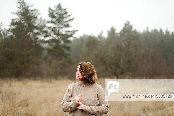 Frau steht bei nebligem Wetter am Wald