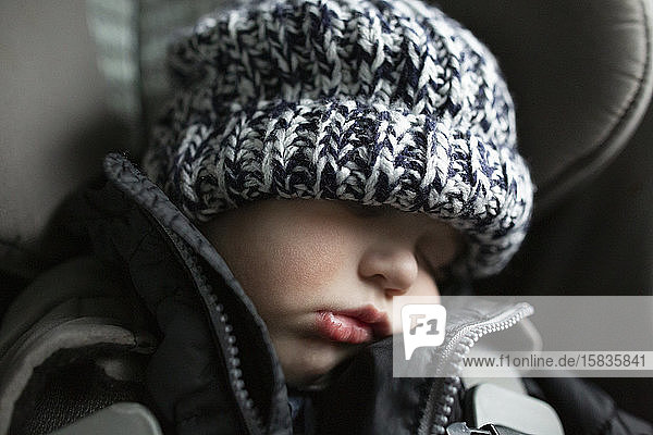 Close-up of toddler boy asleep in carseat while traveling in car