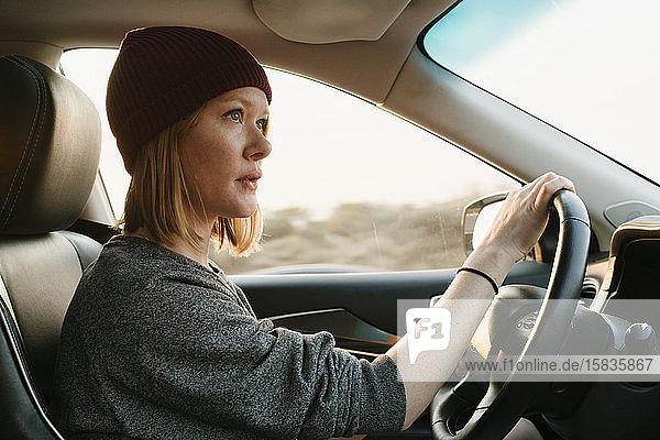 Innenansicht einer Frau  die bei Sonnenuntergang in Big Sur fährt