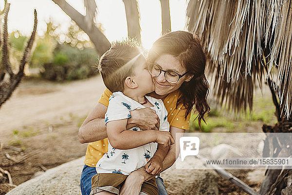 Junger Sohn umarmt und küsst die Mutter auf einem Felsen im sonnigen Kaktusgarten