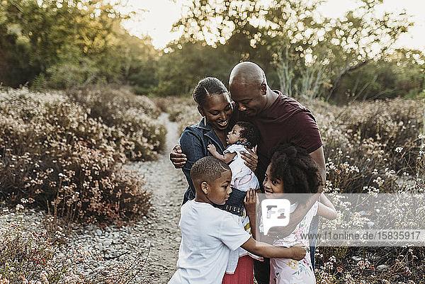 Nahaufnahme einer glücklichen Familie  die ein Neugeborenes im Blumenfeld umarmt