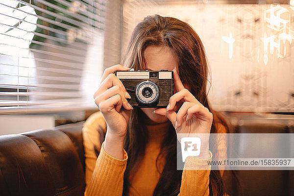 Teenager-Mädchen fotografiert mit Vintage-Kamera  während sie im Café sitzt