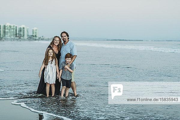 Porträt einer vierköpfigen Familie im Meer in der Abenddämmerung  die in die Kamera lächelt