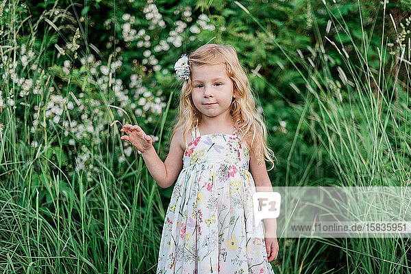 A little girl standing in a meadow.