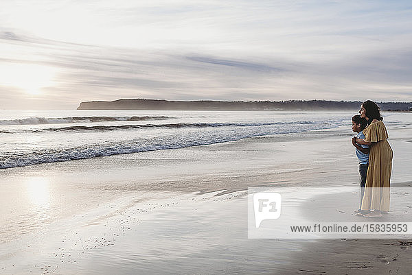Seitenansicht der Landschaft von junger Mutter und Sohn am Meeresufer bei Sonnenuntergang