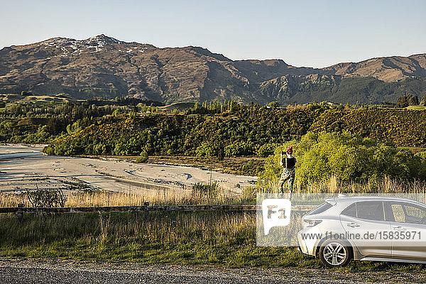 Frau und Auto mit Blick auf eine Fluss- und Berglandschaft  Neuseeland