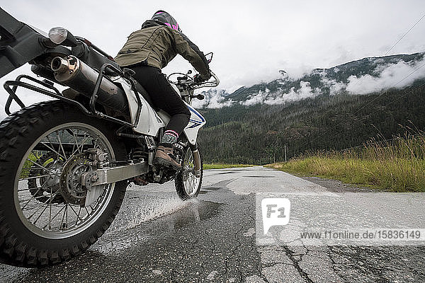 Eine Frau fährt mit ihrem Motorrad an einem bewölkten Sommertag.