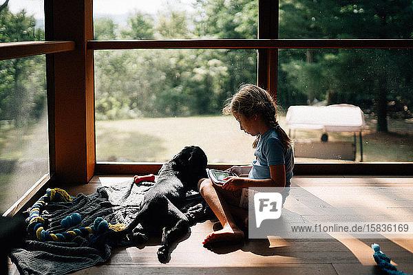 Ein kleines Mädchen sitzt mit ihrem Hund auf einer Veranda.