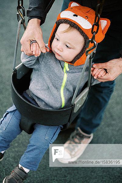 Kleiner Junge mit schwingendem Fuchshut auf dem Spielplatz.