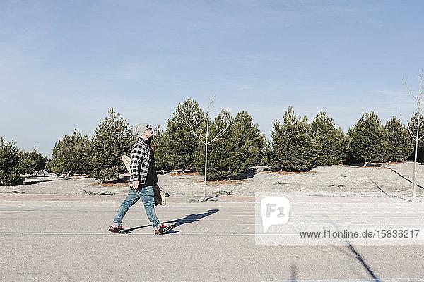Mann geht mit seinem Longboard