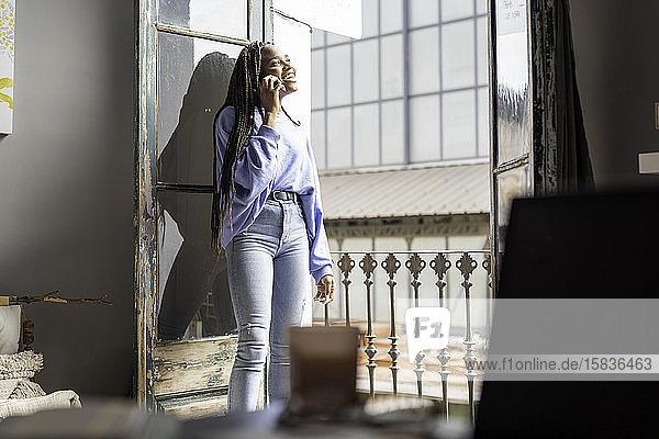 Mädchen telefoniert auf dem Balkon ihres Hauses