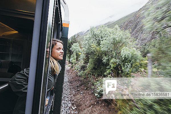 Eine junge Frau schaut aus einem Fenster auf dem Weg nach Machu Picchu