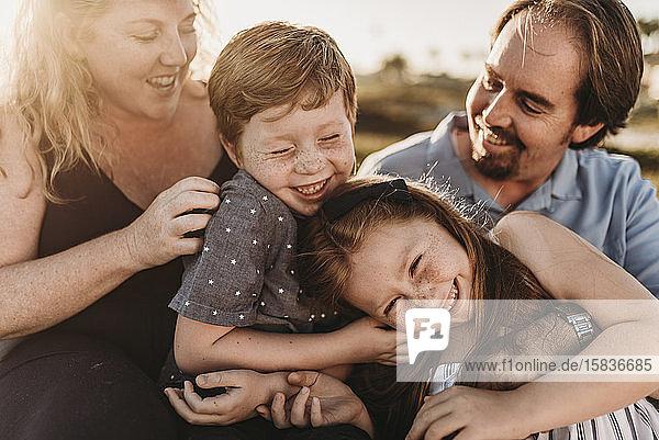 Detailaufnahme einer vierköpfigen Familie  die bei Sonnenuntergang am Strand spielt