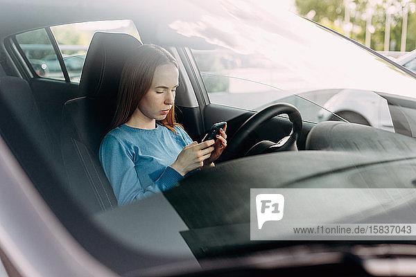 Seriöse Frau hält ihr Smartphone in der Hand  während sie im Auto sitzt.
