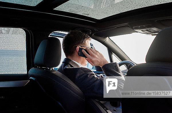 Geschäftsmann telefoniert zu Hause in seinem frostigen Auto