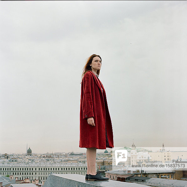 Bildnis einer schönen brünetten Frau in rotem Mantel auf dem Dach stehend