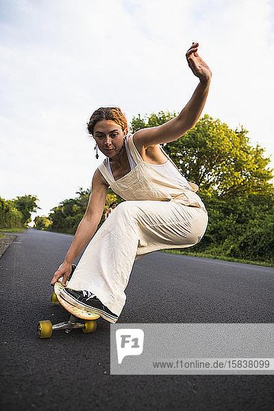 Junge Frau beim Skateboarden im Sommer