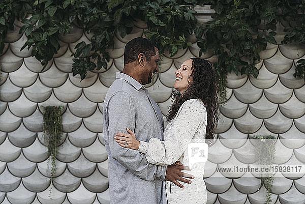 Porträt eines Ehepaares  das sich draußen umarmt und anlächelt