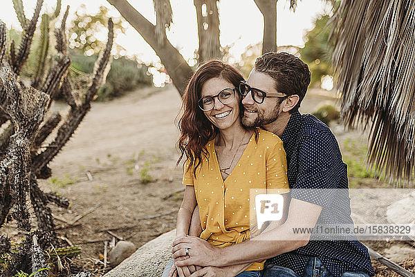 Mittelgroßes erwachsenes Paar umarmt sich lächelnd auf einem Felsen  während sie sich umarmen