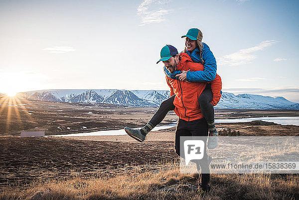 Mann trägt Frau huckepack im Feld mit Bergen im Hintergrund