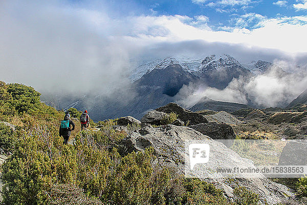 Hikers walking through the cloudy mountains under blue skies in NZ.