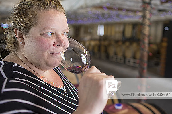 Young woman smelling aromas of red wine at winery.