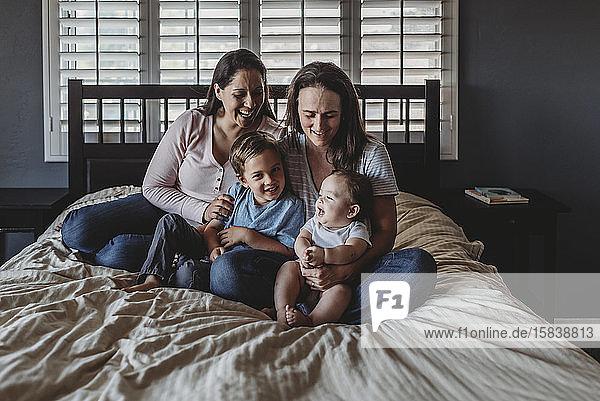 Lachende gleichgeschlechtliche Pärchenfamilie sitzt zusammen auf dem Bett der Mutter