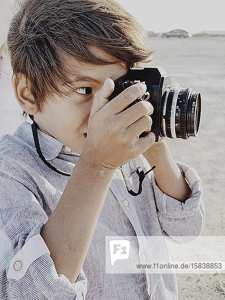 Close up portrait of a child taking a photo with a vintage camera