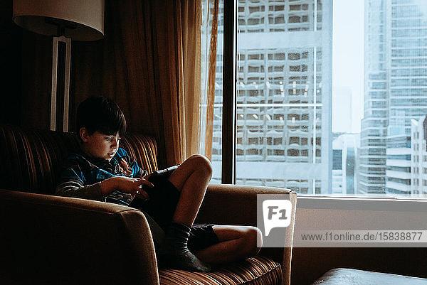 Junge mit Tablett im Stuhl neben dem Fenster mit hohen Gebäuden im Freien.
