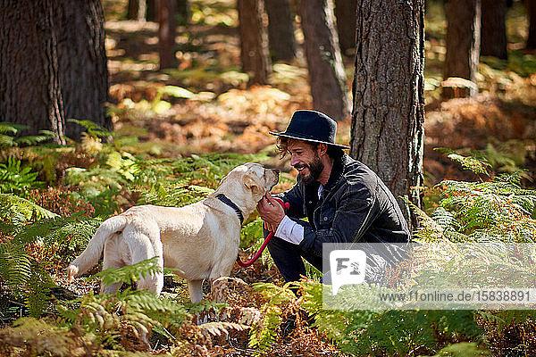 Porträt eines jungen tätowierten Mannes mit seinem Hund im Wald