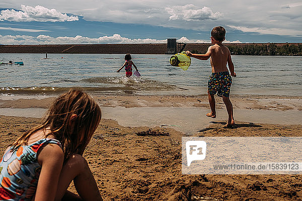 young children playing in sand at a lake in summer