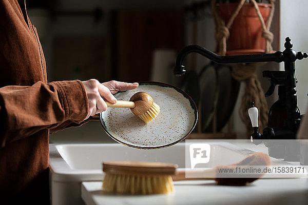 Frau wäscht einen Teller in der Küche mit umweltfreundlichen Bürsten Frau wäscht einen Teller in der Küche mit umweltfreundlichen Bürsten