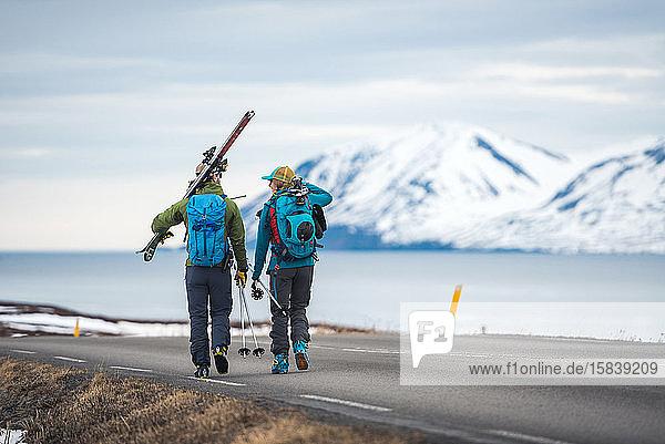 Ein Ehepaar geht in Island mit Skiausrüstung eine Straße entlang