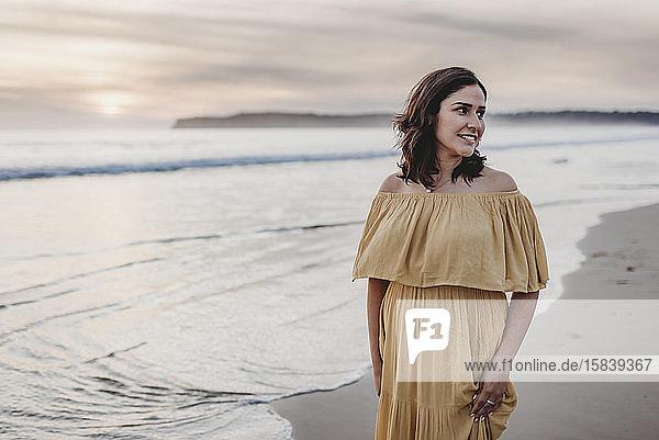 Lifestyle-Porträt einer jungen Frau  die am Strand vor bewölktem Himmel steht