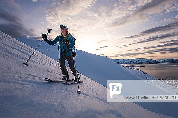 Frau beim Skilanglauf in Island bei Sonnenaufgang mit Wasser im Rücken