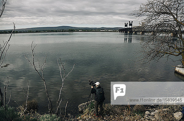A young man films a boat on the Columbia River in Oregon.