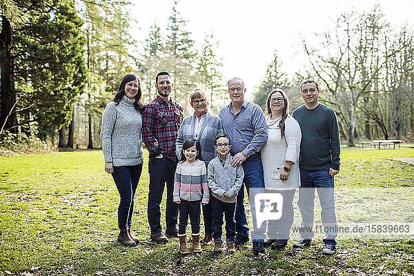 Achtköpfige Familie  die im Park für Fotos posiert.