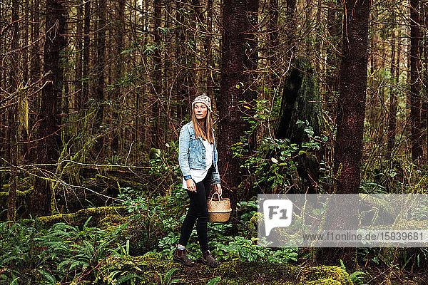 Schöne Frau sucht im Regenwald bei Tofino nach Futter