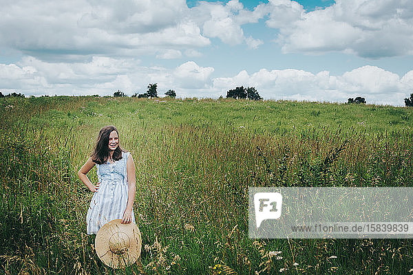 Teen Girl Standing in a Grassy Field Holding a Sun Hat on a Windy Day.