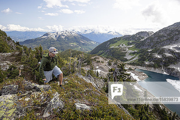 A man hikes along an alpine ridge in the mountains.