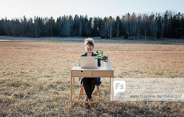 Frau  die flexibel an einem Schreibtisch und Laptop im Freien auf einem Feld arbeitet