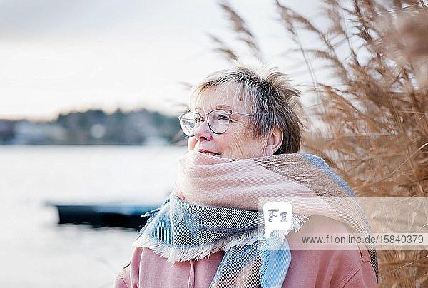Porträt einer Frau in den 60er Jahren  die glücklich aussieht und im Herbst draußen sitzt.
