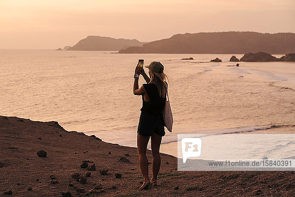 Junge Frau an der Küste bei Sonnenuntergang