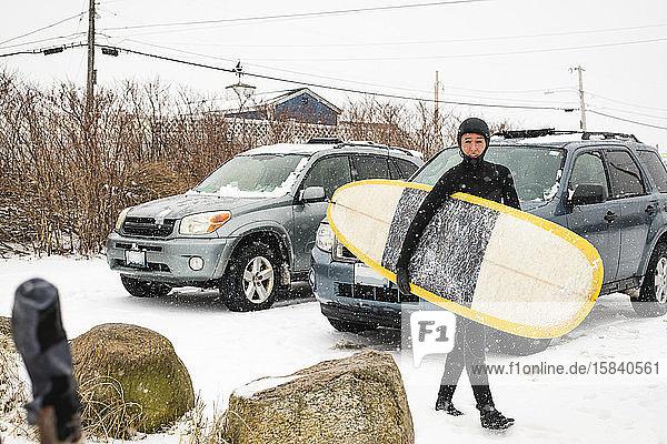 Frau macht sich an einem verschneiten Tag zum Surfen bereit