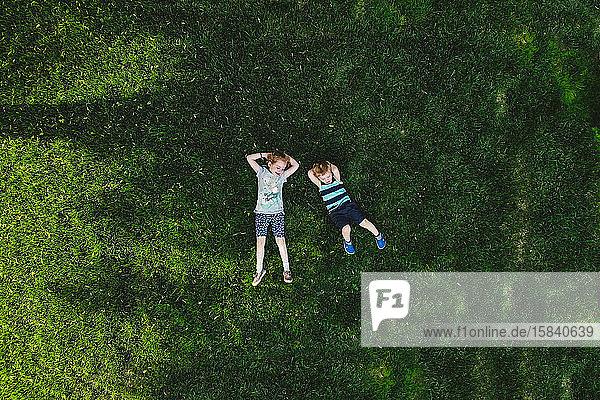 Ein Drohnenschuss auf zwei Kinder  die auf einem grünen Rasen liegen.