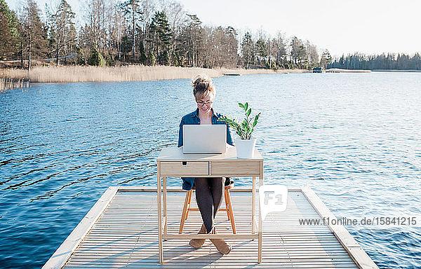 Frau  die flexibel am Schreibtisch auf einem Pier am Strand arbeitet
