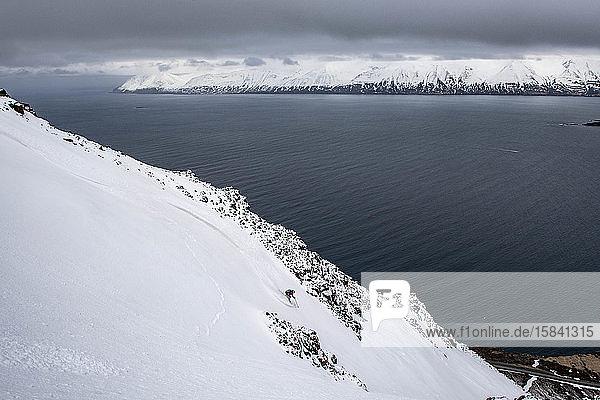 Eine Frau  die in Island Skilanglauf bis zum Meer betreibt.